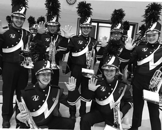 SAY CHEESE: Marching band members pose to show off their hot pink gloves and ribbons on Friday, Oct. 7.