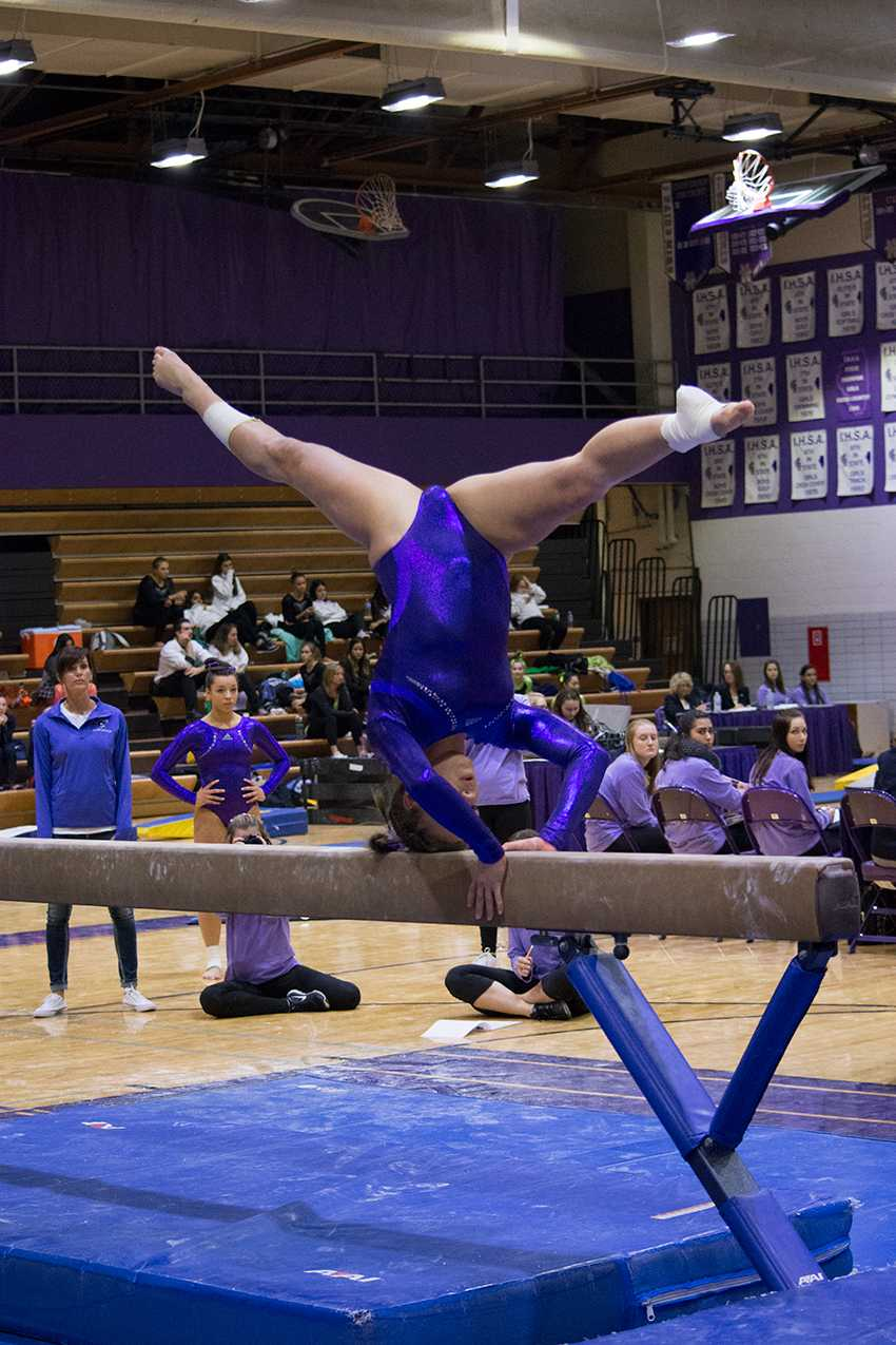HOLD IT STEADY: Brooke Stocki (11) balances on her head during her beam routine at the Big Purple meet.