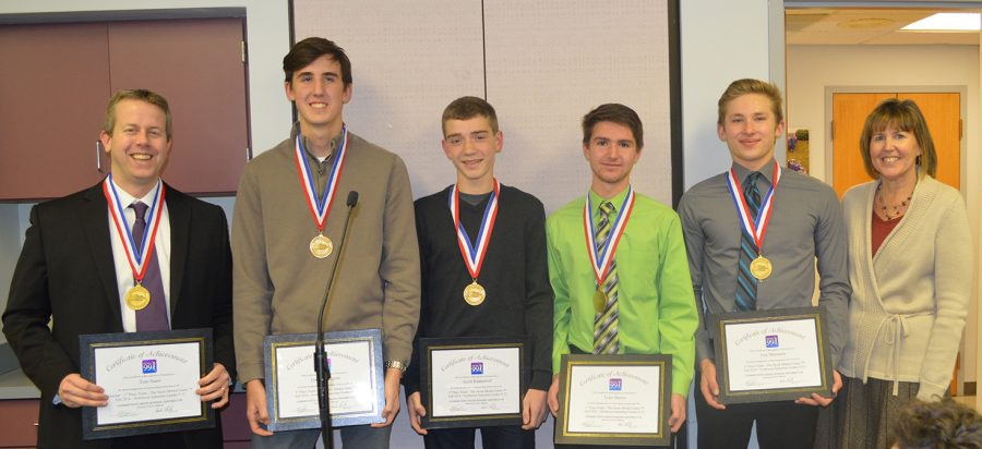 SHOWING THEIR SUCCESS: Champions of the statewide stock market game stand alongside their teacher during the D99 BOE awards ceremony on Jan. 9.