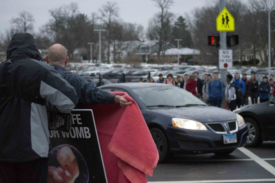DGN social worker Brian Kittenger holds a blanket over an anti-abortion protester's sign.