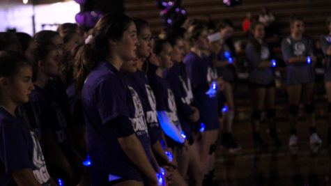 LIGHT IN THE DARK: The freshman, sophomore, and varsity teams all shown wearing glowing bracelets listening to the varsity Coach Wasik. Students bought the wristbands at the Main Street entrance during the week.