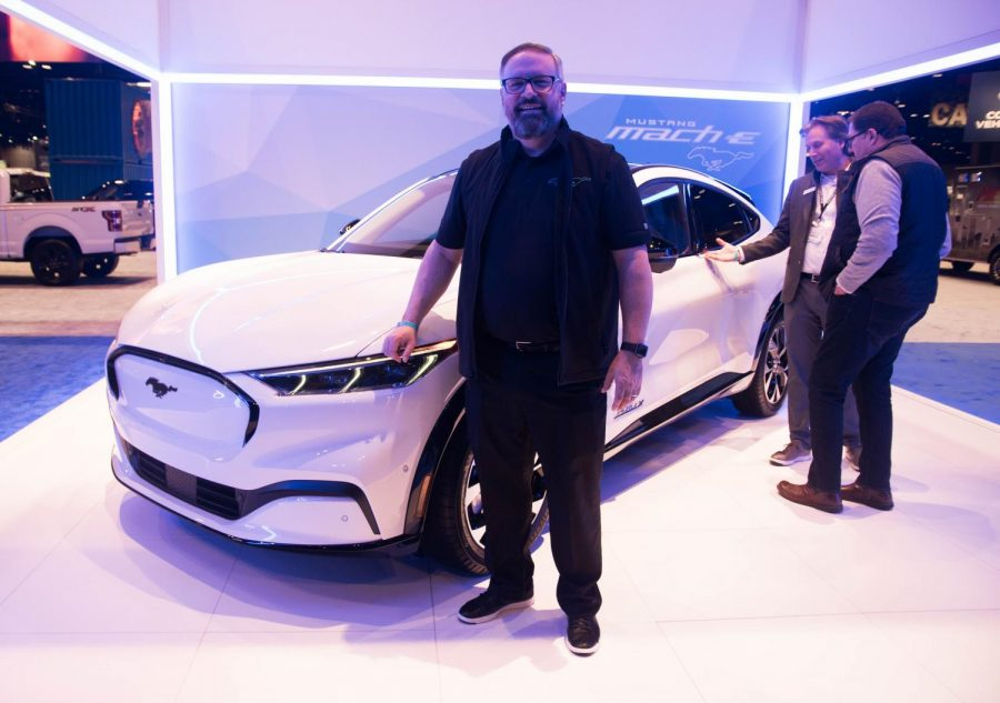 MACH-E MASTERMIND: Ford Marketing Manager and Electrification Marketing Strategist Jason Mase poses next to the new Mustang Mach-E at the Chicago Auto Show Feb. 6 as other journalists check out the car for the first time.