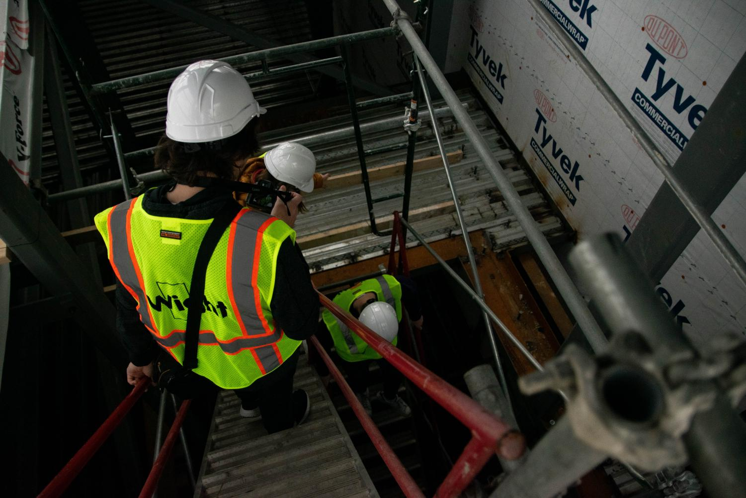 The visiting Omega staff members descend the temporary staircase where the new student elevator will be. This new elevator will go all the way from the third floor down to the underground track.