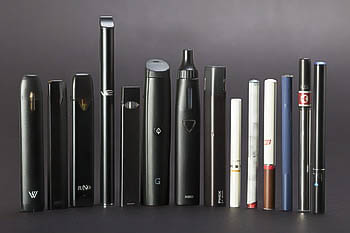 An assortment of e-cigarettes and vapes, including JUUL, PHIX, and STIG.