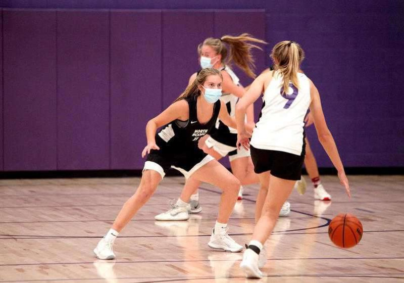 Making plays in masks: Girls' varsity basketball team practices while following safety protocol.