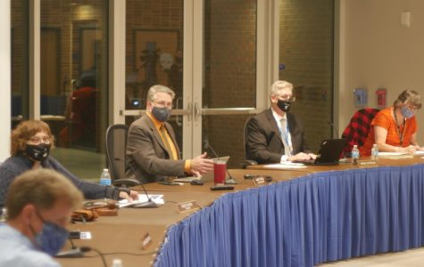 PLANNING FOR THE FUTURE: Dr. Hank Thiele (center left) goes through a presentation at the Board meeting Oct. 19 concerning the return to school.