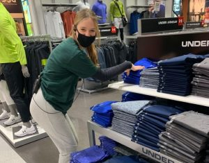 Re-stoked and ready to go: Emily Bormann (11) displays clothes onto shelves in Dicks Sporting Goods as costumers shop.