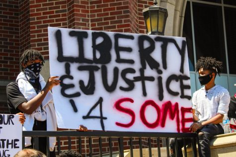 "THE FIGHT FOR EQUALITY: two young men hold a sign reading ""Liberty and Justice 4 Some"" at a BLM march in Downers Grove last summer."