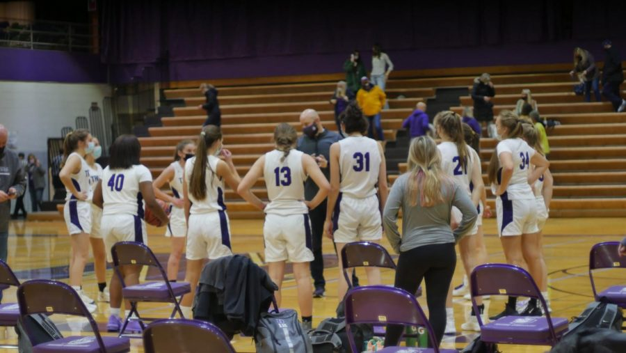 HUDDLE UP: Varsity basketball team talks over the game plan during a time out.
