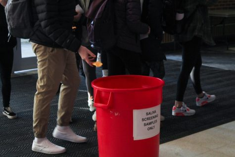 DROP OFF: Students place their saliva tubules in a designated bucket on Feb. 18