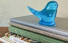 BALLAD OF THE BLUEBIRD: Perched on top of a stack of books is a bluebird figurine, gifted to Madeline Riske by her grandmother. (Photo provided by Madeline Riske)
