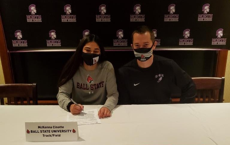 SIGNING THE DOTTED LINE: McKenna Cinotte (12) makes her final decision in committing to Ball State University Nov. 11. She sits with Head Track and Field Coach Matthew Maletich for support of her future.
