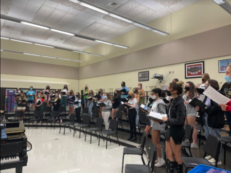 BACK TOGETHER: Treble choir students sing together in risers after a year of separation.