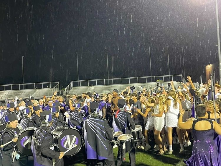DESPITE THE RAIN: DGN players are met on the field by a swarm of spectators including the drumline, color guard and student section.
