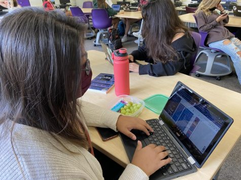 Getting to work: Jade Toledano (12) works on her page in the yearbook program, Yearbook Avenue.