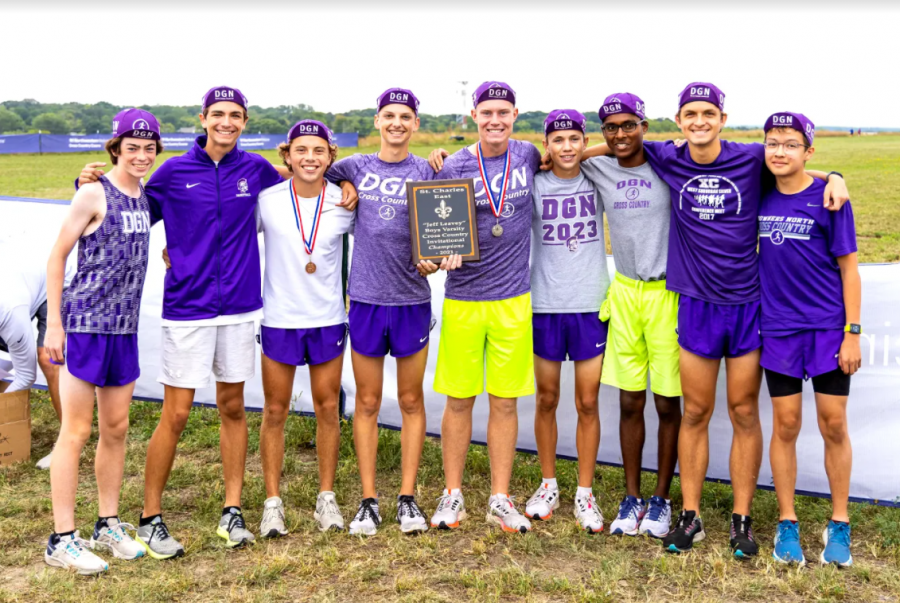 SHOWING OFF THE WIN: Varsity boys cross country team poses with their first place plaque at the St. Charles Invitational.
